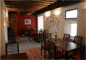 Sala de comedor con mesas de madera y alfombras rojas