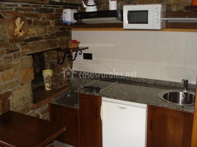 Cocina con paredes de piedra y azulejos blancos