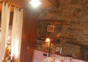 Dormitorio con paredes de piedra y techo de madera