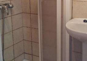 Baño con plato de ducha y azulejos blancos