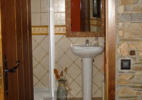 Baño con espejo sobre el lavabo y plato de ducha
