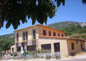 Acceso al alojamiento con fachada en amarillo y piedra
