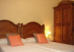 Dormitorio doble con cabecero en madera y cuadros