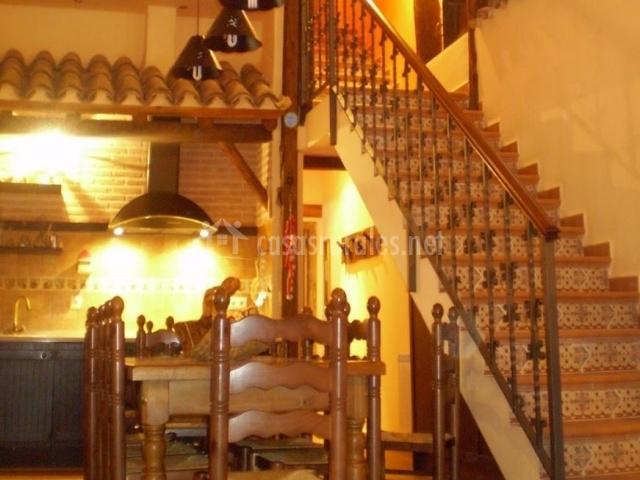 Cocina con mesa para comer y escaleras de acceso a la planta superior