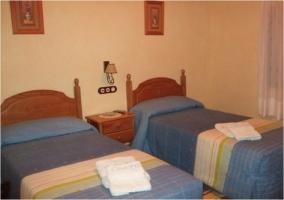 Dormitorio de matrimonio con mobiliario de madera y pared de piedra