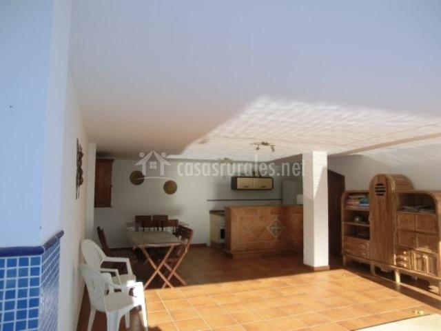 Zona techada con muebles de exterior, cocina y mueble junto a la piscina