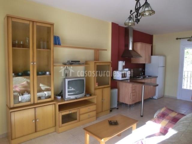Salón con mueble, televisor y cocina al lado en el apartamento