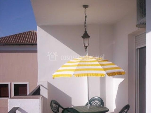 Terraza de apartamento con sillas y mesa de exterior