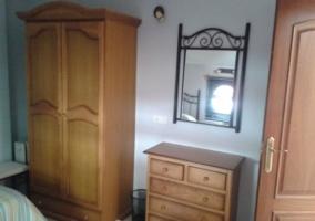 Armario, cajonera y espejo colgado de la pared en dormitorio doble