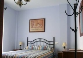 Dormitorio de matrimonio con mesillas y cuadro de adorno