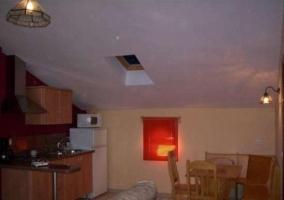 Salón comedor y cocina en misma estancia del apartamento con techo abuhardillado