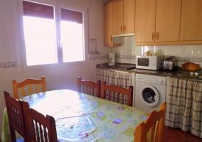 Cocina con distintos electrodomésticos. Mesa y sillas