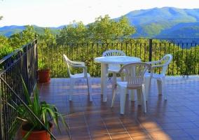 Terraza con mobiliario blanco. Barandilla de hierro y plantas