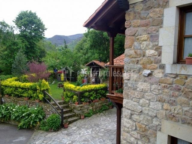 Jardín con zona de césped para comer al aire libre y barbacoa de leña