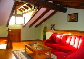 Sala de estar abuhardillada con sofás rojos