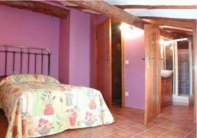 Habitación color morado con cama de matrimonio y baño