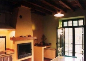 Sala de estar sur con chimenea y cocina