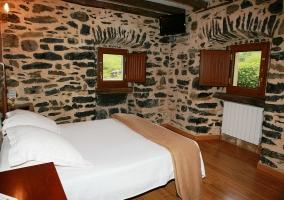 Apartamento cama de matrimonio y contraventanas de madera y pared de piedra