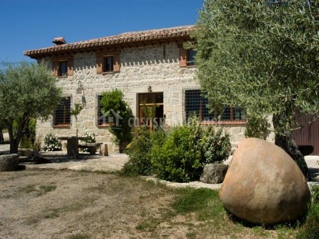 entrada de la casa con jardn olivos y bancos de piedra