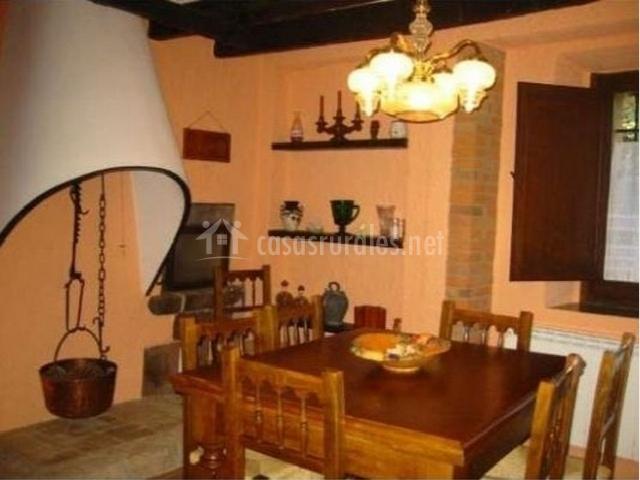 Comedor con mesa de madera y sillas y antigua chimenea