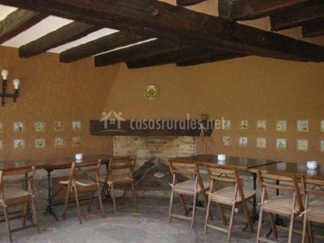 Comedor con varias mesas con sillas y chimenea