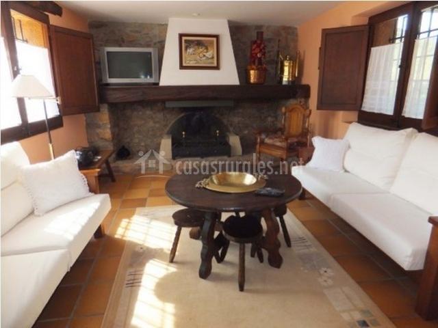 Salón con chimenea de leña, sofás y mesa redonda