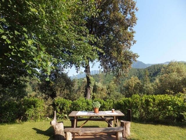 Mesa de troncos de madera en el jardín de la Masía