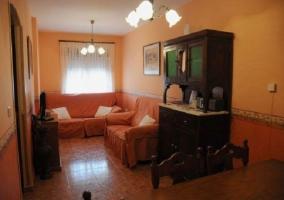 Sala de estar con dos sillones naranjas y televisor sobre mueble