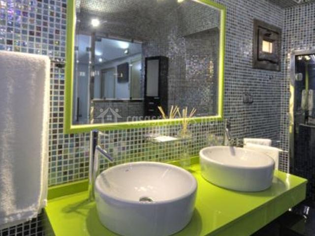 Baño con lavabos en verde