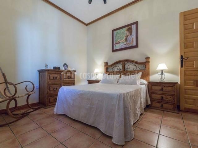 Dormitorio cama grande y mecedora