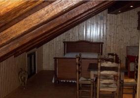 Buhardilla con cama de matrimonio, mesa y sillas