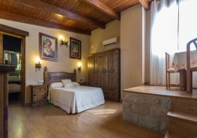 Habitación con cama de matrimonio y techo de madera