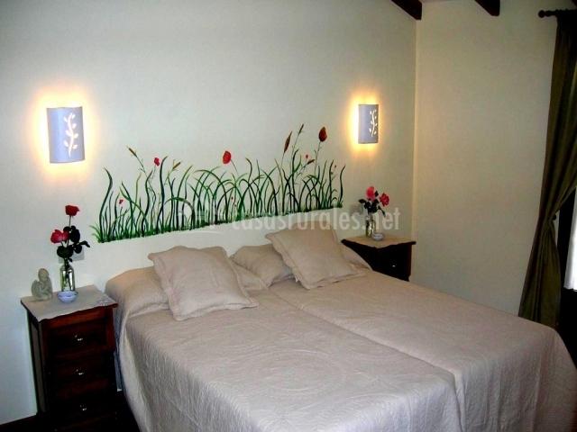 Dormitorio con dos cama juntas y pintura en la pared