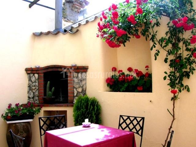 Patio con mesa y barbacoa integrada en la pared