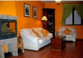 Sala de estar con dos sillones blancos y chimenea con cristal