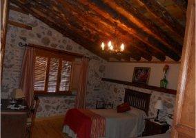 Habitación doble con ventana y pared de piedra