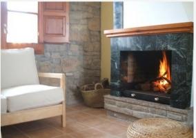Chimenea con sofás de madera en casa rural
