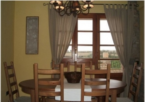 Mesa y sillas de madera en salón con puerta de madera en casa rural