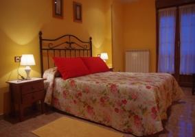 Dormitorio de matrimonio con colcha de flores y mesilla