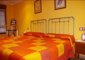 Dormitorio doble con detalles en rojos naranjas y amarillos