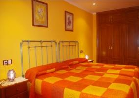 Dormitorio doble con paredes amarillas y armario empotrado