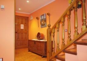 Entrada a la casa con muebles y escaleras en madera