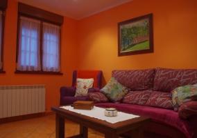 Sala de estar en naranja con sillones tapizados y ventanas