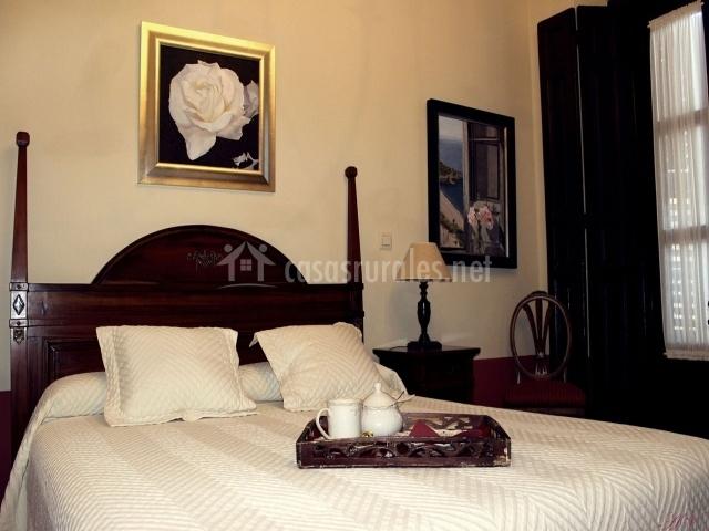 Dormitorio con cama de matrimonio y cuadros