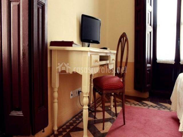 Escritorio con televisor y silla roja