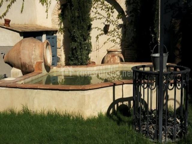 Fuente con vasijas y pozo en el jardin