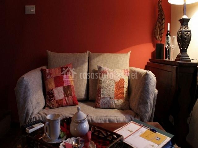 Sala con sillón, mesa y cojines