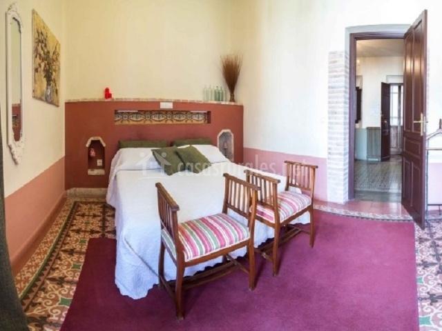 Vista del dormitorio con cama doble y murete