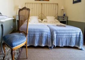 Dos camas individuales y silla azul en el dormitorio