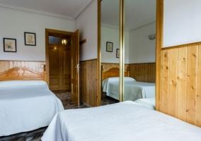 Dormitorio con varias camas y detalles de madera